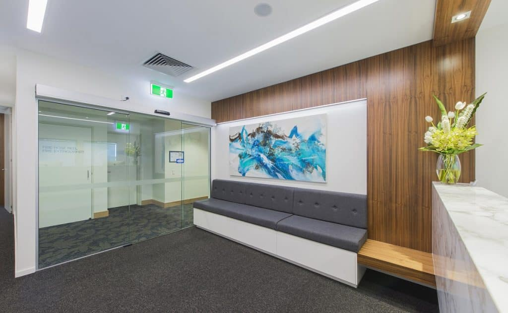 A sliding door makes a clean and uncluttered entrance for this specialist suite fitout